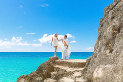 Happy groom and bride on the rock. Turquoise sea in the backgrou Stock Image