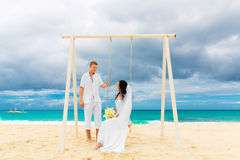 Happy groom and bride on the sandy tropical beach. Wedding and h. Oneymoon concept Royalty Free Stock Photos