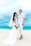 Happy groom and bride on the sandy tropical beach. Wedding and h. Oneymoon concept Stock Image