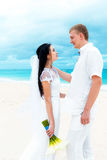 Happy groom and bride on the sandy tropical beach. Wedding and h. Oneymoon concept Stock Images