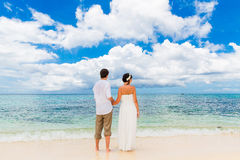 Happy groom and bride on the sandy tropical beach. Wedding and h. Oneymoon concept Stock Photo