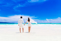 Happy groom and bride on the sandy tropical beach. Wedding and h. Oneymoon concept stock photos