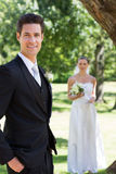 Happy groom with bride standing in background at garden Royalty Free Stock Image