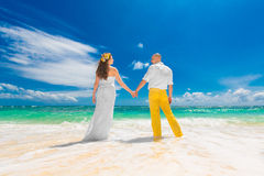 Happy groom and bride standing with his back to the viewer on th Royalty Free Stock Photos