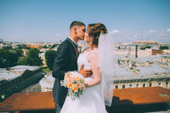 Happy groom and bride are standing on the roof Stock Photo