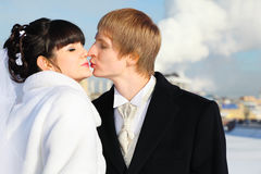 Happy groom and bride tender kiss at winter Stock Image