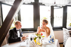 Happy groom and bride  together in cafe having fun. Happy newlywed couple at wedding Stock Photos