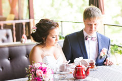 Happy groom and bride  together in cafe having fun. Happy newlywed couple at wedding Stock Photo