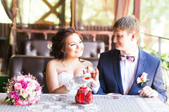 Happy groom and bride  together in cafe having fun. Happy newlywed couple at wedding Royalty Free Stock Photo