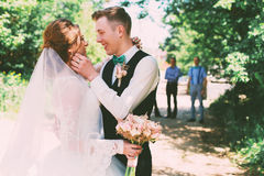 Happy groom and bride under tree on road Royalty Free Stock Photography