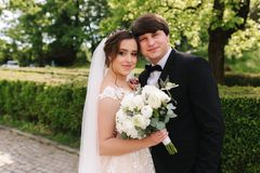 Happy groom and bride walking in the park. Charming woman with handsome man spend time together. Happy groom and bride walking in the park. Charming women with stock photos