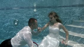 Happy groom and bride in white wedding dress sitting underwater on the bottom of the pool. The bridegroom floats and kisses the bride`s hand. Portrait. Zoom stock footage