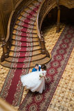 Happy groom carry his wife near big wooden stairs at old vintage house, top view Royalty Free Stock Photography
