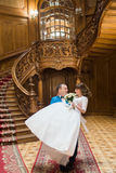 Happy groom carrying his wife with bouquet near big wooden stairs at old vintage house Royalty Free Stock Images