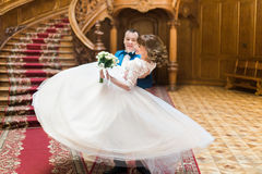 Happy groom carrying his wife with bouquet near big wooden stairs at old vintage house Royalty Free Stock Photography