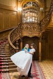 Happy groom carrying his wife with bouquet near big wooden stairs at old vintage house Stock Photos