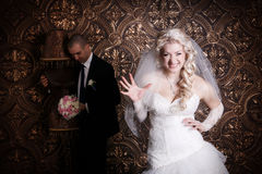 Happy groom and the charming bride with a bouquet from roses in studio Royalty Free Stock Photography