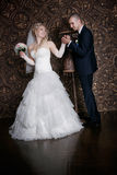 Happy groom and the charming bride with a bouquet from roses in studio Stock Image