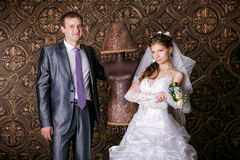 Happy groom and the charming bride with a bouquet from roses in studio Royalty Free Stock Images