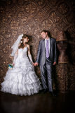 Happy groom and the charming bride with a bouquet from roses in studio Stock Photos