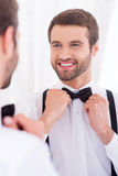 Happy groom. Close-up of young man in white shirt adjusting his bow tie and smiling while standing against mirror royalty free stock image