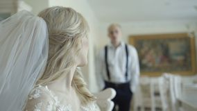 Happy groom comes with smile to smart bride in luxurious apartment stock footage