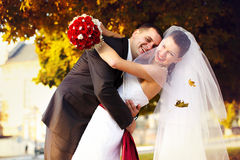 Happy groom embraces a bride under autumn trees Stock Photography