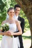 Happy groom embracing bride from behind in garden Stock Photo