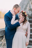 Happy groom embracing with his pretty bride while both stand on antique stone stairs. Half length portrait.  Stock Image