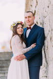 Happy groom embracing with his pretty bride while both stand on antique stone stairs. Half-length portrait.  Stock Image