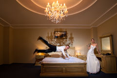 Happy groom flying on bed Stock Photos