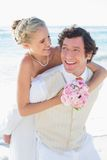 Happy groom giving his blonde wife a piggy back Royalty Free Stock Photos