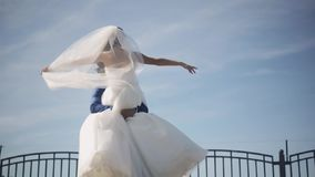 Happy groom hold on hands his bride in white wedding dress and turning around. Newlyweds enjoy sunny day. Slow motion. stock footage