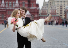 Happy groom holding beautiful bride stock images