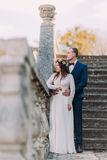 Happy groom holding his pretty bride while both stand on antique stone stairs. Full length portrait.  Royalty Free Stock Photo