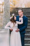 Happy groom holding his pretty bride while both stand on antique stone stairs. Half-length portrait.  Royalty Free Stock Photo