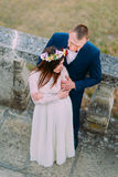 Happy groom holding his pretty bride while both stand on antique stone stairs. High angle view Stock Photo