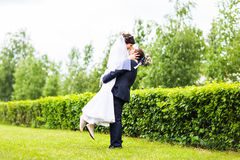 Happy groom holding young beautiful bride in his arms Stock Photos