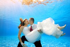 The happy groom holds the bride in his arms underwater in the pool and kisses her on the background of sunlight. Portrait. Shooting under water. Landscape Stock Photo
