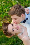 Happy groom kisses the bride on cheek. Spring walk Royalty Free Stock Photos