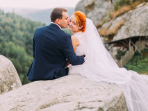 Happy groom kisses redhair bride. Cute romantic moment. Back view with Carpatian landscape Royalty Free Stock Photography