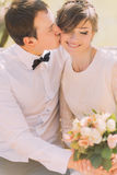 Happy groom kissing smiling blonde bride with bouquet on the cheek. Spring walk Royalty Free Stock Image