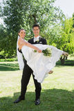 Happy groom lifting bride in arms at garden Royalty Free Stock Images