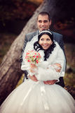 Happy groom and the pretty bride in autumn park Stock Photo