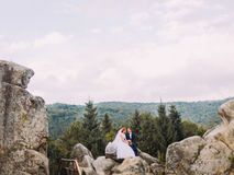 Happy groom and redhair bride with long veil sitting on the stone. Carpathian mountains background. Happy groom and redhair bride with long veil sitting on the Stock Photo