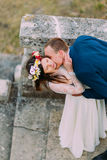 Happy groom sagging his pretty bride while kiss her on antique stone stairs. High angle view.  Royalty Free Stock Photography