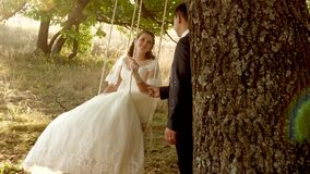 Happy groom swinging on a swing the bride in the park in summer. Boy and girl swing on a branch of an oak in the summer stock video footage