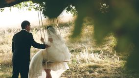 Happy groom swinging on a swing the bride in the park in summer. teamwork of a couple in love. boy and girl swing on a stock footage