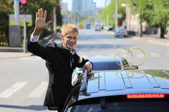 Happy groom waving from wedding car Stock Image
