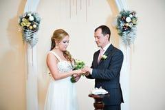 Happy groom wears wedding ring his bride Royalty Free Stock Image